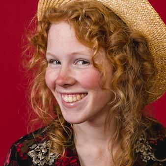 Het vrolijke jonge toothy glimlachen van de roodharigevrouw