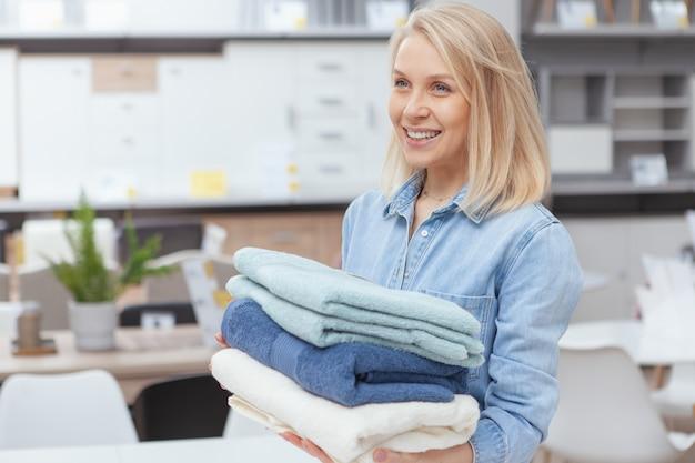 Het vrolijke jonge vrouw genieten die winkelend bij meubilairopslag, katoenen handdoeken houden