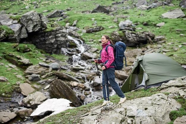 Het vrolijke jonge vrouwenwandelaar glimlachen die in de bergenvallei lopen met trekkingsstokken, tent op de achtergrond