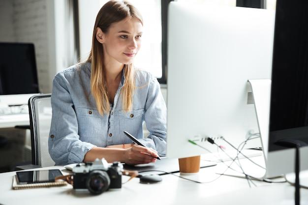 Het vrolijke jonge vrouwenwerk in bureau dat computer met behulp van