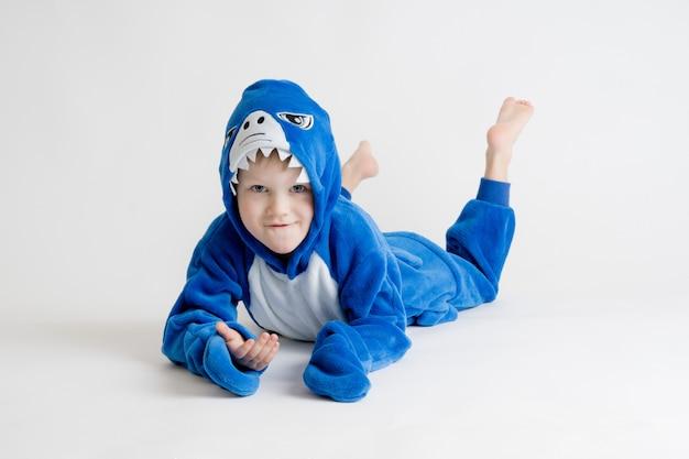 Het vrolijke kleine jongen stellen op een witte achtergrond in pyjama kigurumi, blauw haaikostuum