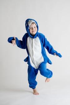Het vrolijke kleine jongen stellen op een witte achtergrond in pyjama'skigurumi, blauw haaikostuum