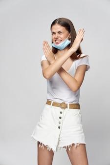 Het vrolijke medische masker van de vrouw kruiste haar wapens voor haar witte t-shirt