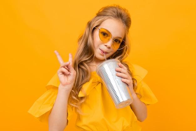 Het vrolijke meisje drinkt een coctail en glimlacht geïsoleerd op gele achtergrond