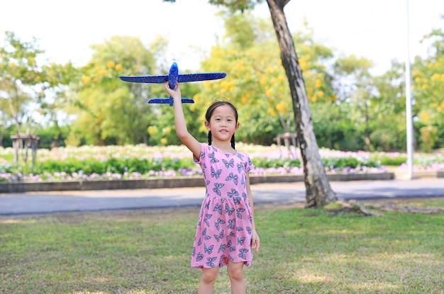 Het vrolijke meisje heft een blauw stuk speelgoed vliegtuig op dat op lucht in de tuin vliegt openlucht.