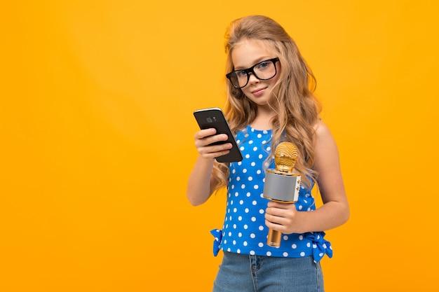 Het vrolijke meisje met een microfoon verweeft en glimlacht geïsoleerd op geel