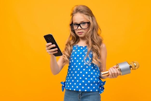 Het vrolijke meisje met een microfoon verweeft en glimlacht geïsoleerd op gele achtergrond