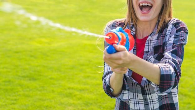 Het vrolijke meisje spelen met waterkanon