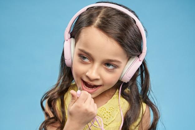 Het vrolijke meisje stellen, die in roze hoofdtelefoons dragen.