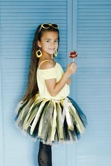 Het vrolijke meisje stellen met smiley-vormige lolly