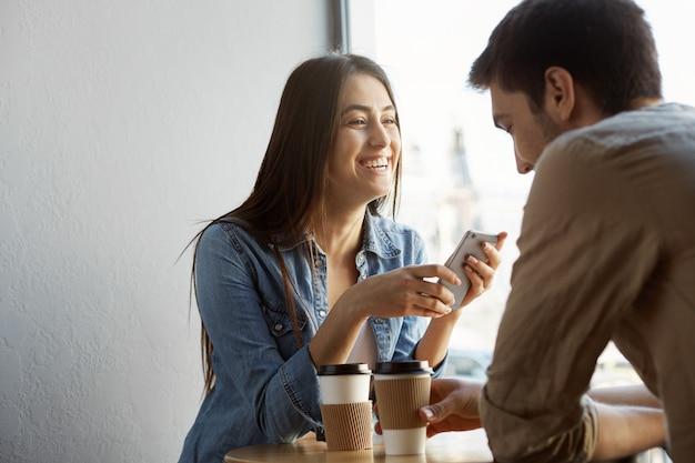 Het vrolijke mooie meisje met donker haar zit in koffie op datum, lachend en grappige verhalen uit het leven vertellend aan haar vriend. warme sfeer van geluk.