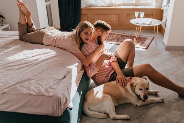Het vrolijke paar heeft pret in slaapkamer en speelt met hond die op vloer ligt. meisje lacht en knuffelt vriendje.
