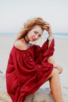 Het vrolijke red-head meisje stellen op strand. zittend op wit zand. winderige haren. stijlvolle outfit. lifestyle portret. reisstemming. oceaan kust.