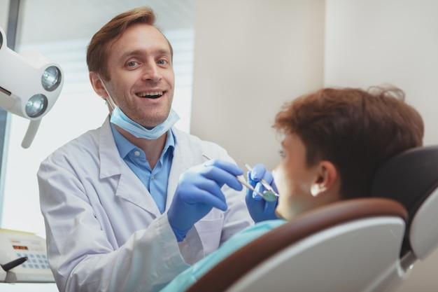 Het vrolijke rijpe mannelijke tandarts genieten die bij zijn kliniek werken, die tanden van een kleine jongen onderzoeken