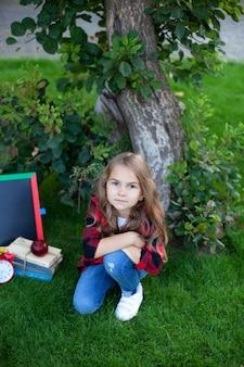 Het vrolijke schoolmeisje houdt stapel boeken in tuin dichtbij school. voorschoolse educatie. terug naar school. glimlachend meisje zitten op groen gras spelen met schoolbord, boeken in park. onderwijs concept.