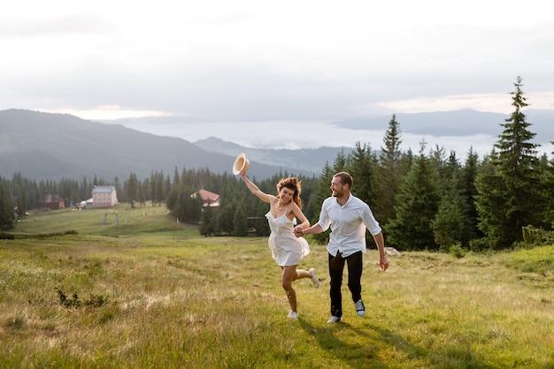Het vrolijke stel rent door de open plek, in het bos en de bergen