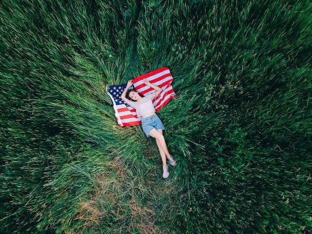 Het vrolijke tienermeisje ligt in het gras op de vlag van de vs.