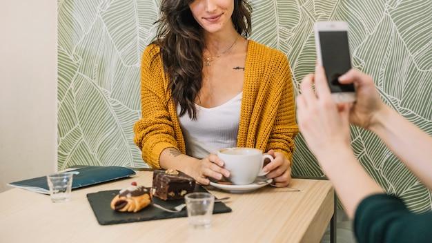 Het vrouw van het gewas het stellen voor foto in koffie