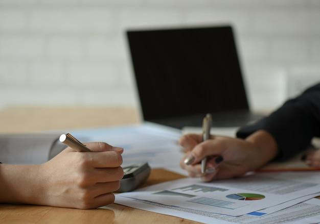 Het vrouwelijke accountantenteam analyseert de gegevens om het budget samen te vatten.