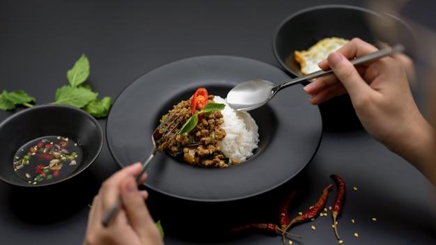 Het vrouwelijke eten beweegt gebraden fijngehakt varkensvlees met basilicum (pad ka prao) op zwarte lijst in thais restaurant