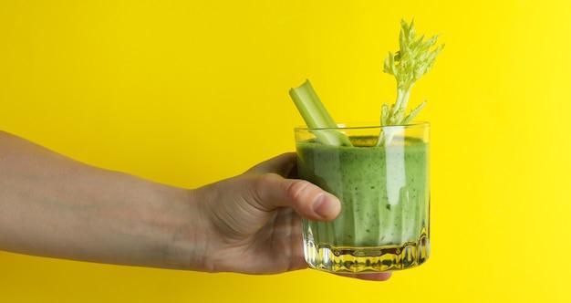 Het vrouwelijke glas van de handgreep smoothie op gele achtergrond