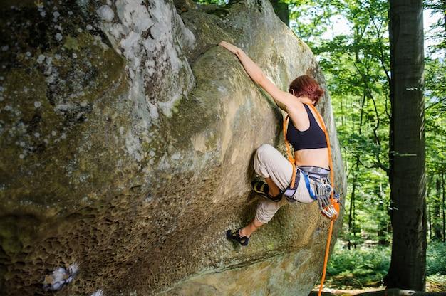 Het vrouwelijke grijpende houvast van de rotsklimmer terwijl lood die op een grote kei, met kabel en karabijnen beklimmen