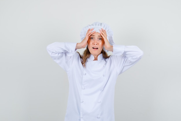 Het vrouwelijke hoofd van de chef-kokholding met dient wit uniform in en kijkt vermoeid