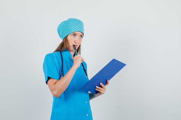 Het vrouwelijke klembord en de pen van de artsenholding in blauw uniform en het kijken bezet. vooraanzicht.