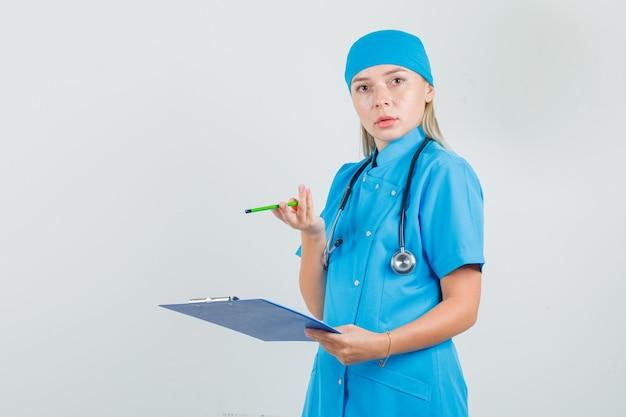 Het vrouwelijke klembord en het potlood van de artsenholding in blauw uniform en het kijken verward