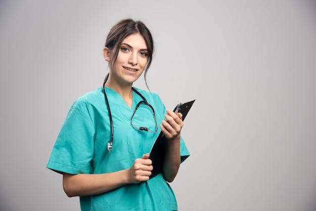 Het vrouwelijke klembord van de artsenholding op grijs