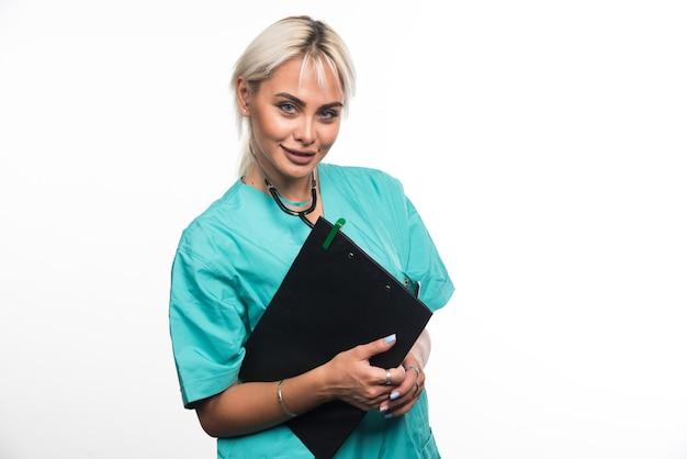 Het vrouwelijke klembord van de artsenholding op wit oppervlak