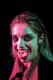 Het vrouwelijke model dat van halloween als joker glimlacht