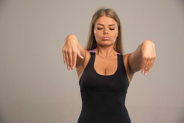 Het vrouwelijke model in sportbeha legt haar handen vooruit.