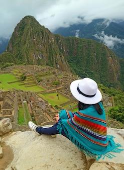 Het vrouwelijke ontspannen op cliff looking bij de ruïnes van machu picchu inca, cusco, peru