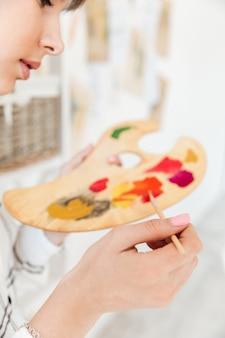 Het vrouwelijke palet van de kunstenaarsholding en het mengen van verfkleuren
