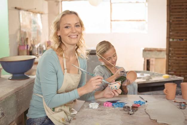 Het vrouwelijke pottenbakker en meisjes schilderen in aardewerkworkshop