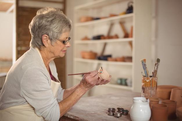 Het vrouwelijke pottenbakker schilderen op kom