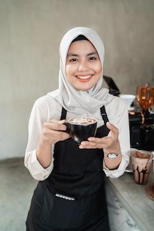 Het vrouwelijke serveerster glimlachen houdt een kop van koffie