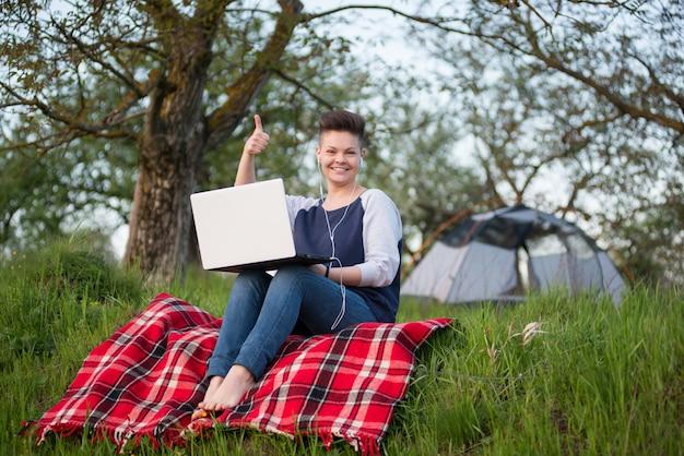 Het vrouwelijke student glimlachen die tonen beduimelt omhoog het werken aan haar laptop terwijl het kamperen in openlucht zittend op het gras voor haar tent