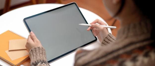 Het vrouwelijke student online leren met modeltablet en kantoorbehoeften op koffietafel in woonkamer