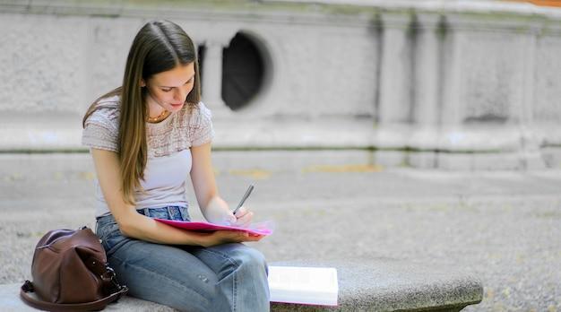 Het vrouwelijke studentenholding lopen openlucht in het park