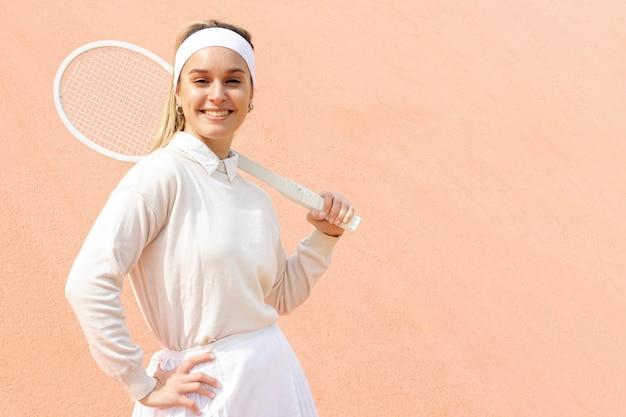 Het vrouwelijke tennisspeler stellen met racket