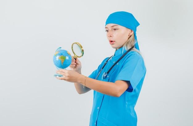 Het vrouwelijke vergrootglas van de artsenholding over bol in blauw uniform en kijkt verbaasd