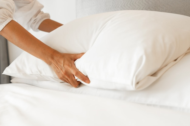 Het vrouwelijke witte laken van de handopstelling in slaapkamer