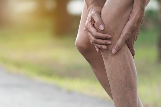 Het vrouwtje klampt zich vast aan een slecht been. de pijn in haar been. gezondheid en pijnlijk concept.