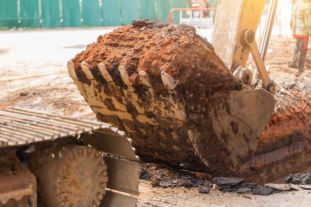 Het vuile graafwerktuig van de backhoebouwwerf met het graven van landgrond bij plicht het werken graaft voor pijp