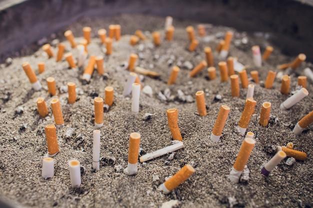 Het vuile hoogtepunt van het staalasbakje van oude sigaret en sigarenuiteinden - dat op wit wordt geïsoleerd.