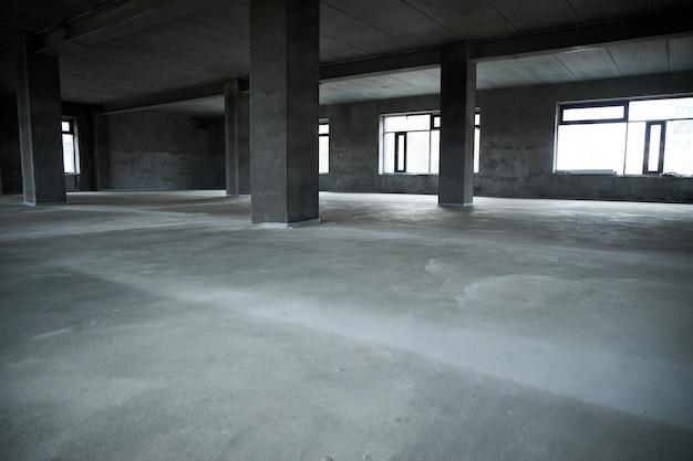 Het vullen van de vloer met beton, dekvloer en het egaliseren van de vloer. gladde vloeren gemaakt van een mengsel van cement, industrieel beton Premium Foto