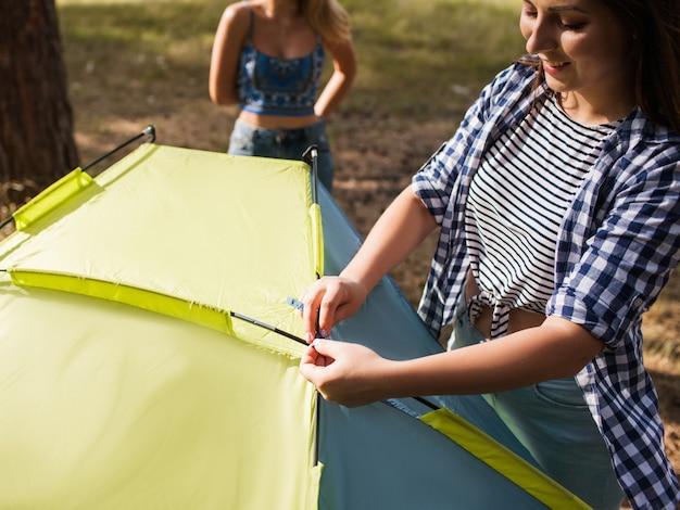 Het wandelaarmeisje bereidt het concept van het tentnatuurtoerisme voor. kampeeruitrusting. eenheid met de natuur