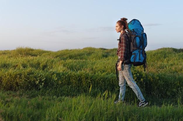 Het wandelaarmeisje reist met een rugzak op de landschapsachtergrond